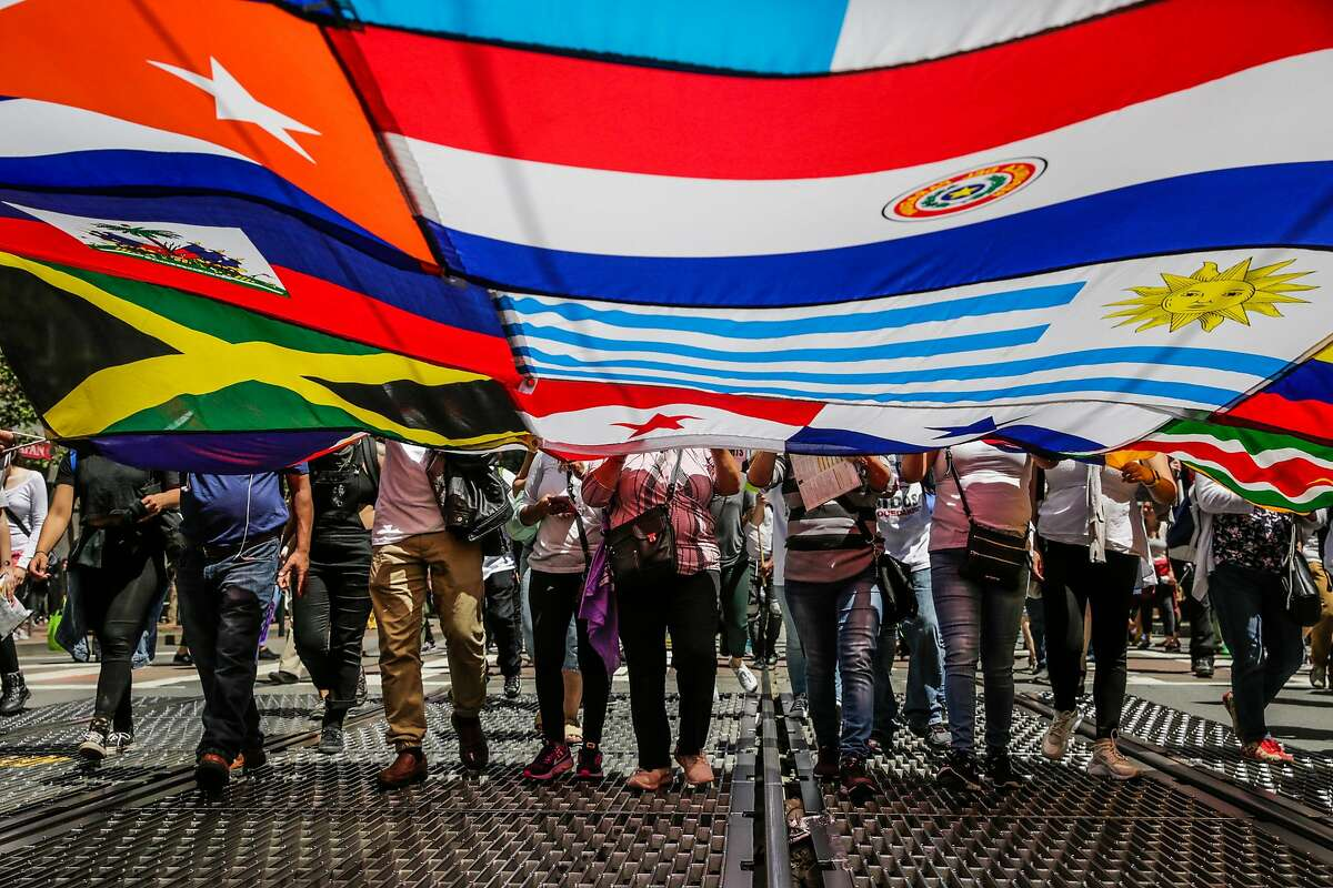 People hold a flag banner as they walk down Market Street during a May Day demonstration in San Francisco on Monday, May 1, 2017.