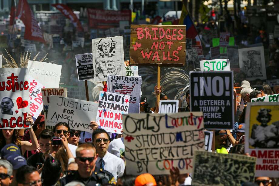 People hold banners as they walk down Market Street during a May Day demonstration in San Francisco on Monday, May 1, 2017. Photo: Gabrielle Lurie, The Chronicle