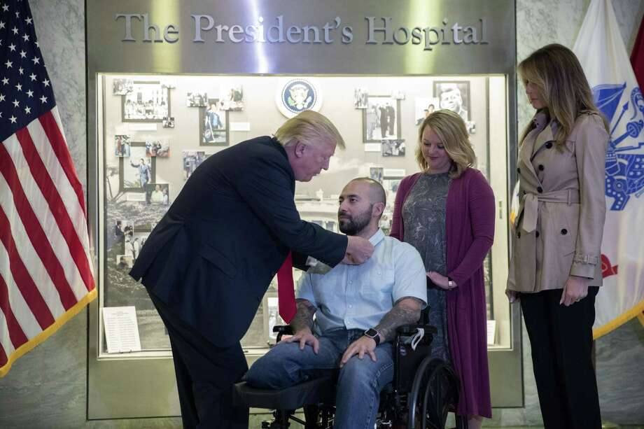 President Donald Trump (L), with First Lady Melania Trump (R), awards Sergeant First Class Alvaro Barrientos the Purple Heart, while his wife, Tammy Barrientos, stands behind him and Photo: Pool / / 2017 Getty Images