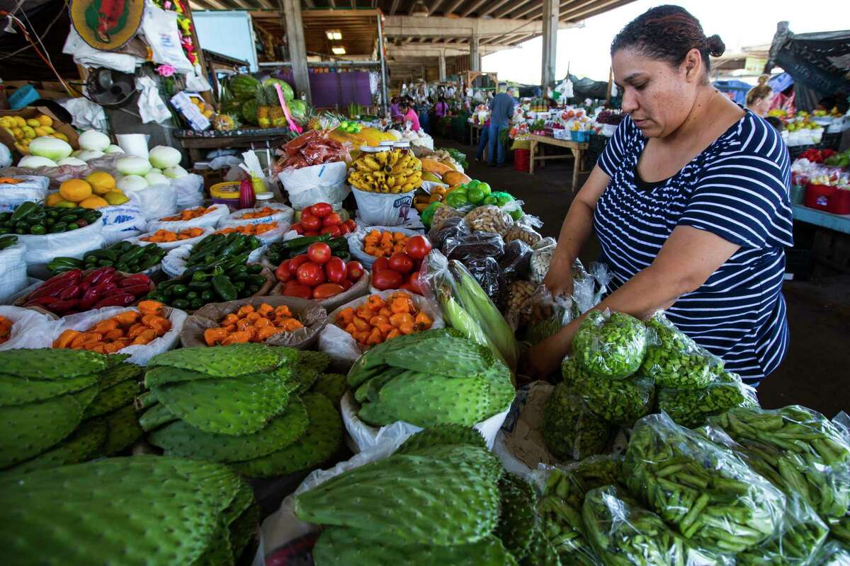 Silvia Salinas sorts produce Monday at the farmers market in the 2500 block of Airline in the northern Heights.