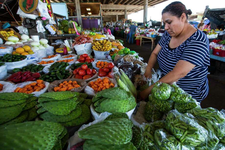 Silvia Salinas sorts produce Monday at the farmers market in the 2500 block of Airline in the northern Heights. Photo: Brett Coomer, Staff / © 2017 Houston Chronicle