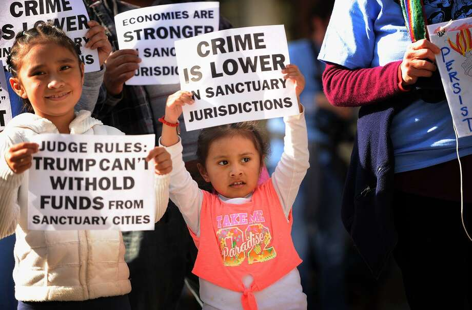 Sisters Fanny, 7, left, and Kelly Huerta, 3, of Bridgeport, hold signs as they march with their family from McLevy Green to City Hall in Bridgeport, Conn. in support of undocumented immigrants on Monday, May 1, 2017. Photo: Brian A. Pounds / Hearst Connecticut Media / Connecticut Post