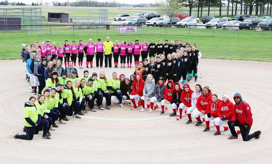 Members of the Ubly, Deckerville, Port Huron Northern and Port Huron High softball form a ribbon, Saturday, during the Striking Out Cancer Softball Tournament, in Deckerville.