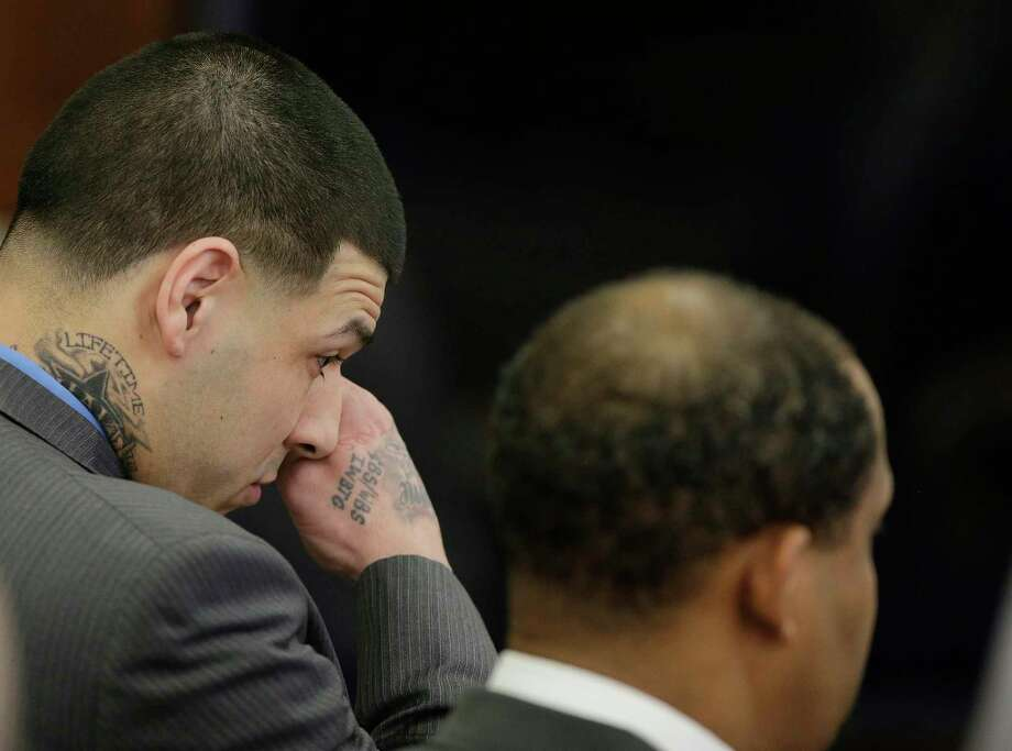 Former New England Patriots tight end Aaron Hernandez wipes tears from his eyes as he stands with defense attorney Ronald Sullivan reacting to his double murder acquittal at Suffolk Superior Court Friday, April 14, 2017 in Boston. Hernandez stood trial for the July 2012 killings of Daniel de Abreu and Safiro Furtado who he encountered in a Boston nightclub. The former NFL player is already serving a life sentence in the 2013 killing of semi-professional football player Odin Lloyd. (AP Photo/Stephan Savoia, Pool) ORG XMIT: MASS105 Photo: Stephan Savoia / Pool AP