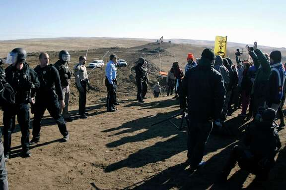 North Dakota says it needs help paying for the expenses of policing the Dakota Access Pipeline protests. In November, law enforcement personnel were trying to move these protesters.