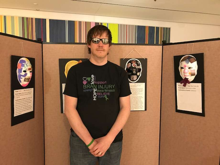 Art Show Unmasking Brain Injury: Conan O'Rourke, BIANYS member, brain injury survivor and Unmasking Brain Injury artist stands proud next to his personal Unmasking Brain Injury display during the kickoff of the Brain Injury Association of New York State Art Show in Albany, NY on Monday April 24. (Submitted photo)