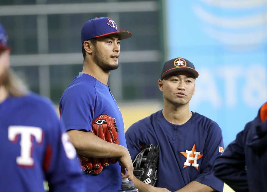 Nori Aoki's (right) quest to reach 2,000 total hits between MLB and Nippon Professional Baseball received extra attention in a faceoff with Rangers starter Yu Darvish (left). Photo: David J. Phillip/Associated Press