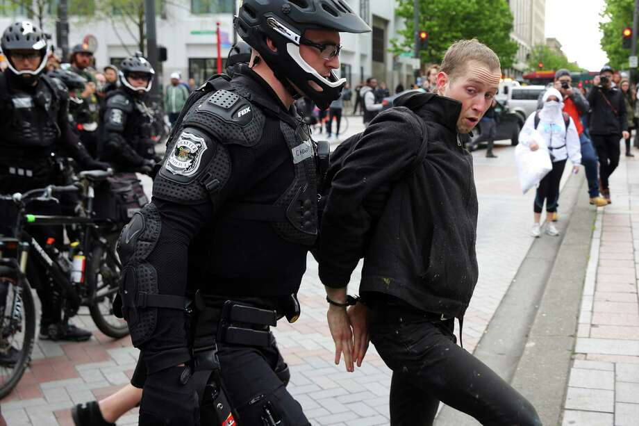 A man is arrested after he allegedly threw a rock as anti-fascist demonstrators clash with Trump supporters and police at Westlake Park during an evening demonstration, May Day 2017 in Seattle. Photo: GENNA MARTIN, SEATTLEPI.COM / SEATTLEPI.COM