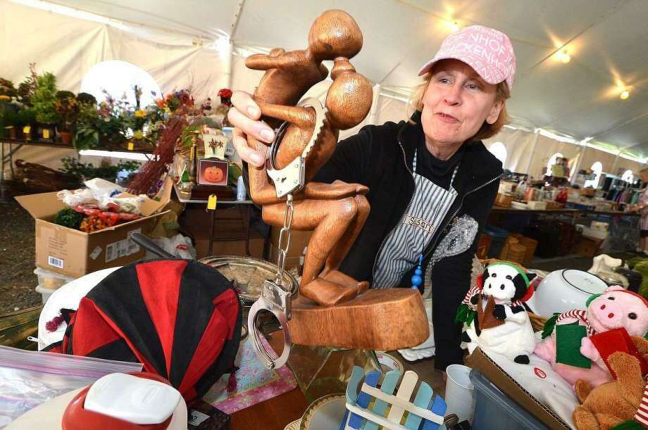 Volunteer Susan Florido organizes some of the items such as a free-form sculpture — handcuffs extra — for the upcoming Minks to Sinks Sale. Photo: Hearst Connecticut Media File