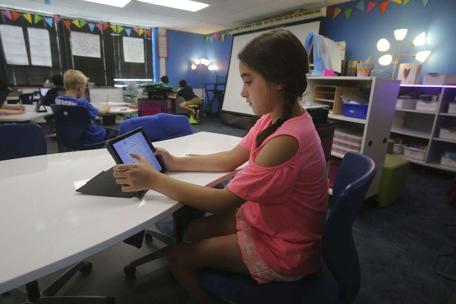 """Madeleine Wallis,9, works on a lesson with an electronic device in Heather Smith's fourth grade reading, writing and social studies class. The subjects are taught in what is called an """"engaged"""" manner that lets kids learn at their own pace with a Google Classroom platform. Wheels are on furniture, lighting is controlled, and tables convert to whiteboards. Wobbly stools are used as well as bean bag chairs. Smith's engaged classroom is one of only 17 in the Alamo Heights District. Photo: John Davenport, STAFF / San Antonio Express-News / ©San Antonio Express-News/John Davenport"""