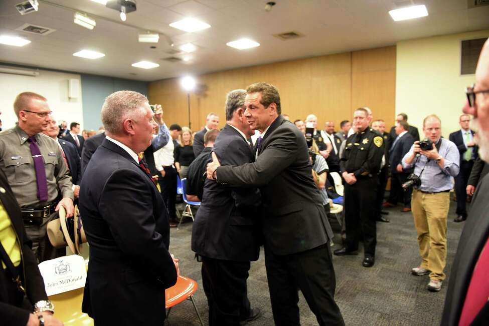 Gov. Andrew Cuomo, right, embraces Sen. Neil Breslin, center, as Assemblyman John T. McDonald III, left, awaits his turn following a press event at the Albany Public Library where the governor announced public safety initiatives on Tuesday morning, May 2, 2017, in Albany, N.Y. (Will Waldron/Times Union)
