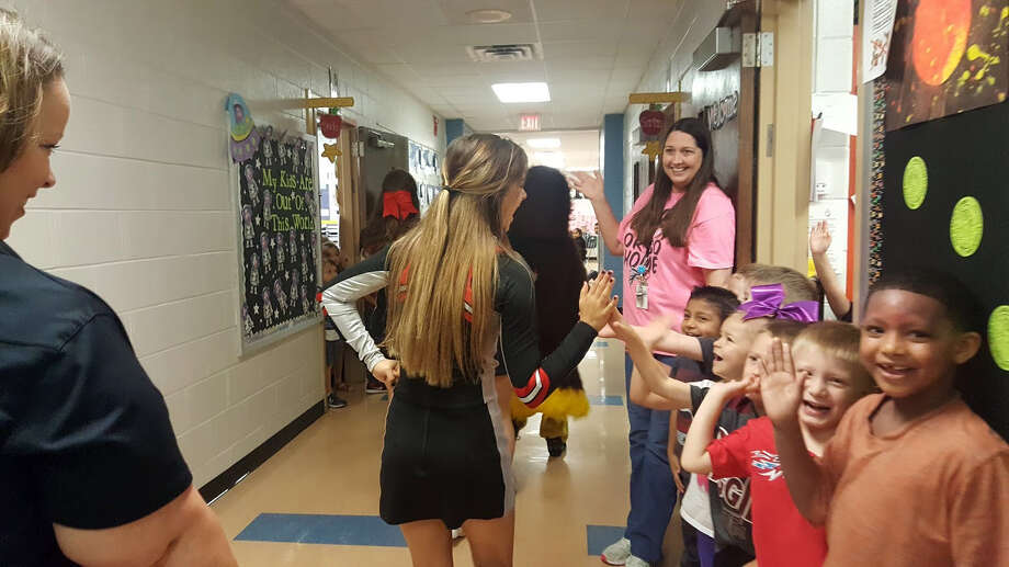 Hargrave High School cheerleaders high-five Ben Bowen Early Childhood Center students during the Huffman Education Foundation Prize Patrol April 28. Photo: Melanie Feuk