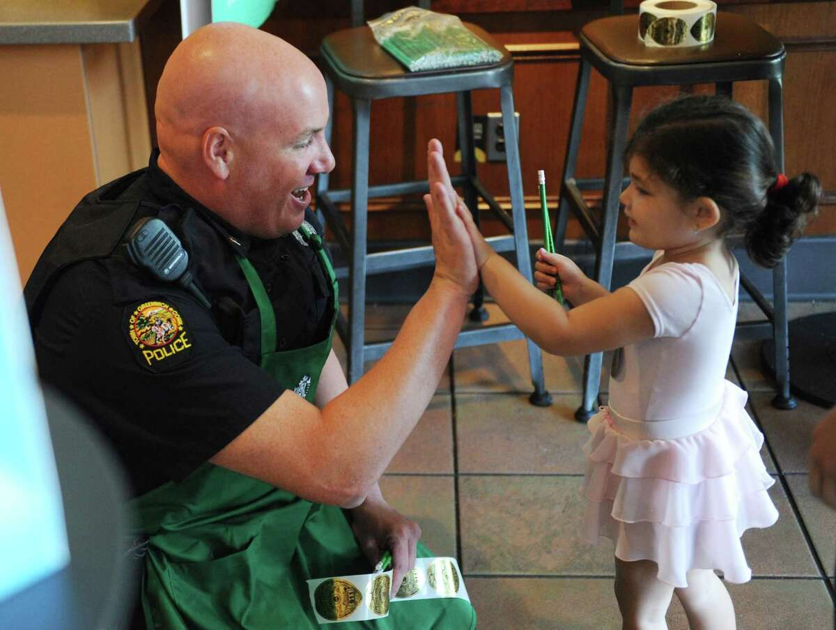 Officer Tom Huestis high-fives Riverside's Nicole Solomon, 3, during the Coffee with a Cop event at the Starbucks in the Riverside section of Greenwich, Conn. Tuesday, May 2, 2017. The event allowed citizens to chat with Greenwich police officers in a casual setting to give them a feel for the men and women behind the uniforms.