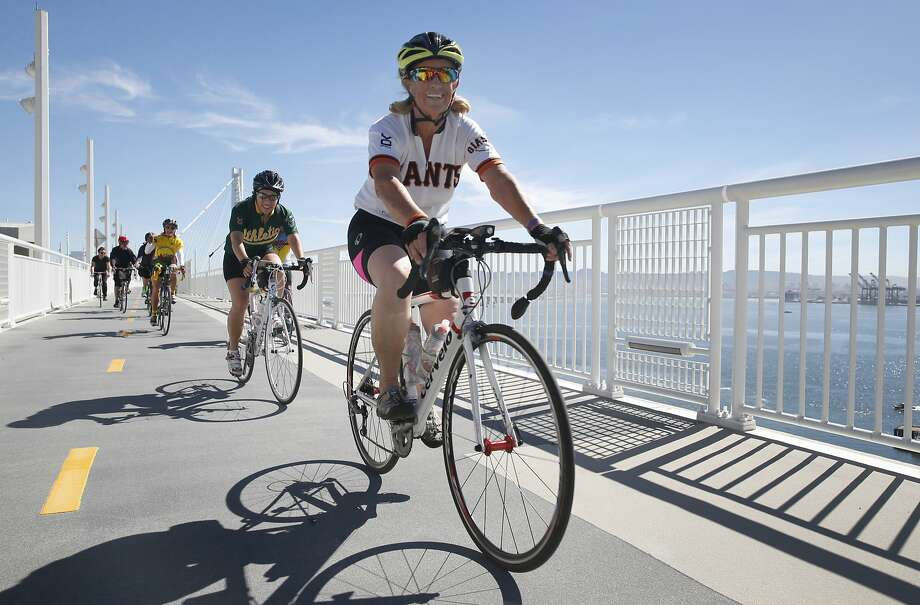 Bicyclists pedal, above, toward Yerba Buena Island from Oakland on the bike path along the eastern span of the Bay Bridge. Jesse Flores, below, opens the island gate to the path, now open on weekdays. Photo: Paul Chinn, The Chronicle