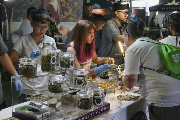 FILE - In this April 23, 2017 file photo Calfarms, a medical marijuana provider help attendees at the High Times Cannabis Cup in San Bernardino, Calif. California is trying to get control of its unruly medical marijuana industry. State regulators released draft regulations Friday, April 28, intended to impose order on the loosely organized marketplace created over two decades ago. The proposal would establish the first comprehensive rules for growing, testing, transporting and selling medical pot in the state that is home to 1 in 8 Americans. (AP Photo/Richard Vogel, File)