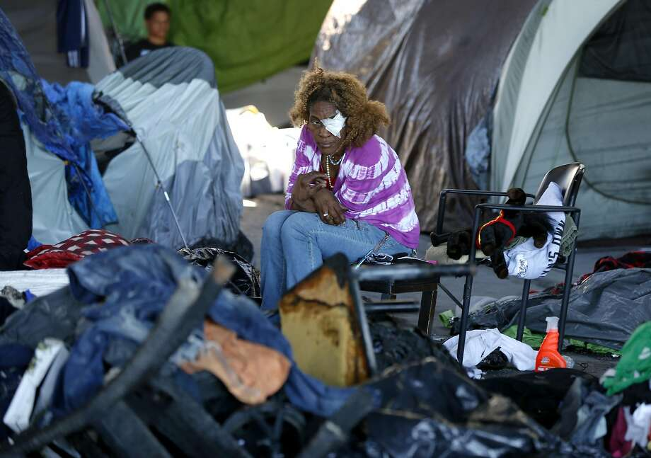 A woman sits with burned items after a fire in a city-backed homeless camp at 35th and Peralta streets below Interstate 580 in Oakland. Photo: Paul Chinn, The Chronicle