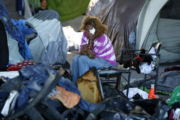 A woman sits with burned items in a homeless encampment at 35th and Peralta streets below Interstate 580 in Oakland, Calif. on Tuesday, May 2, 2017 after a fire torched 20 tents in the city sanctioned camp Monday night.