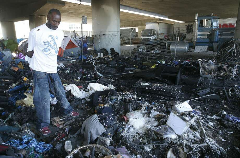 James Reed stands with charred belongings after a fire erupts in a homeless encampment in Oakland, the second blaze at this city-sanctioned tent city. Photo: Paul Chinn, The Chronicle