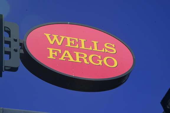 (FILES) This file photo taken on September 28, 2016 shows a Wells Fargo sign in front of a branch in Pasadena, California. The entire Wells Fargo board of directors was reelected on April 25, 2017 after a bruising, rowdy annual meeting where shareholders castigated the bank's leadership over a fake accounts scandal that severely damaged the company's image. Even so five members, including the chairman, received only tepid support from investors.  / AFP PHOTO / Frederic J. BROWNFREDERIC J. BROWN/AFP/Getty Images