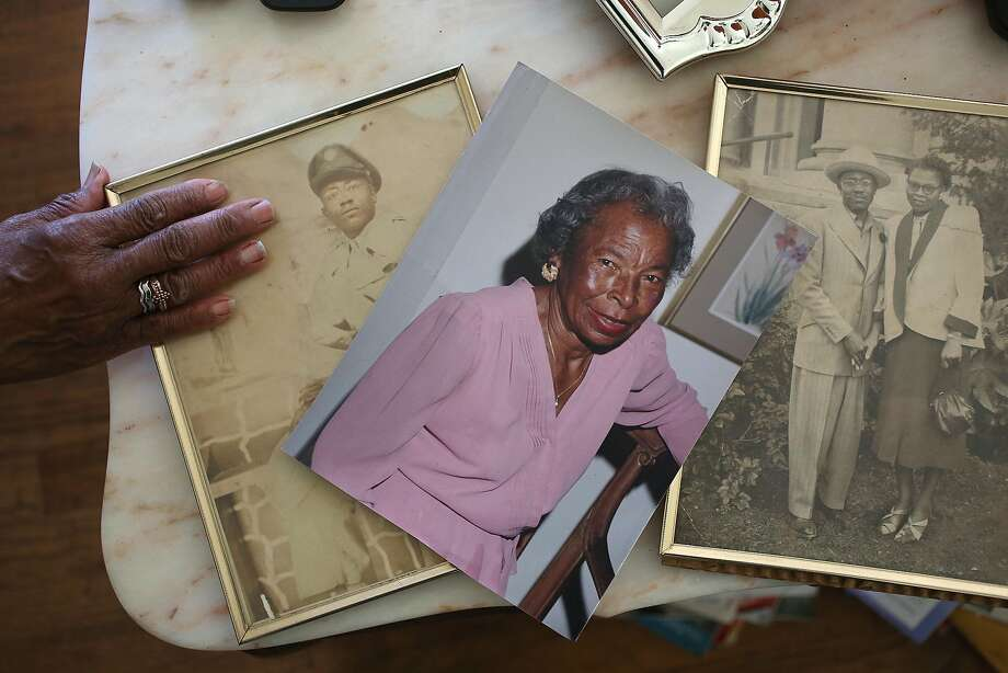 Dorothy DeBose, an East Oakland woman who was evicted from her house in March, and moved back into the home she lost to foreclosure shows pictures of her father and her stepmom back in May. Photo: Liz Hafalia, The Chronicle