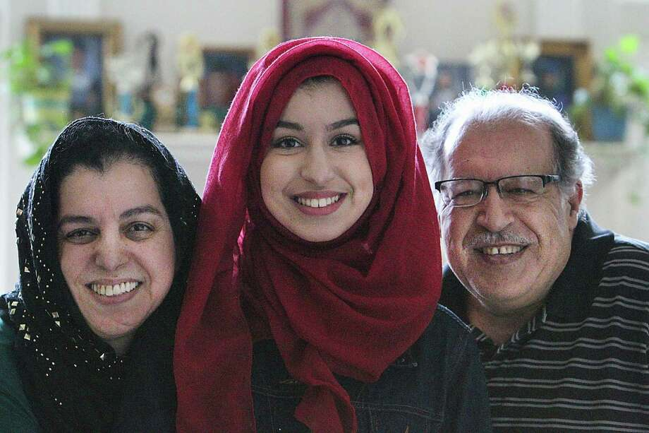 Amina Mabizari is at the top of her class at Alief ISD's Elsik High and accomplished something no other student in Texas has this year: She as accepted into seven of eight Ivy League schools, waitlisted only by Harvard University. Amina (center) and her parents Nadia  (left) and Bachir photographed Friday, April 28, 2017, in Houston. ( Steve Gonzales  / Houston Chronicle ). Photo: Steve Gonzales, Houston Chronicle / © 2017 Houston Chronicle