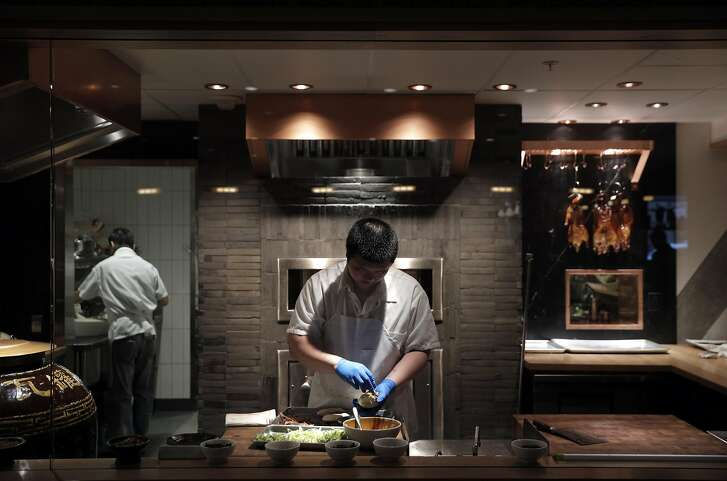 A cook prepares Peking Duck with Kumquat Glaze at the barbecue kitchen at China Live in San Francisco, Calif., on Wednesday, April 26, 2017.  China Live is the new ambitious restaurant and Chinese food emporium in Chinatown.