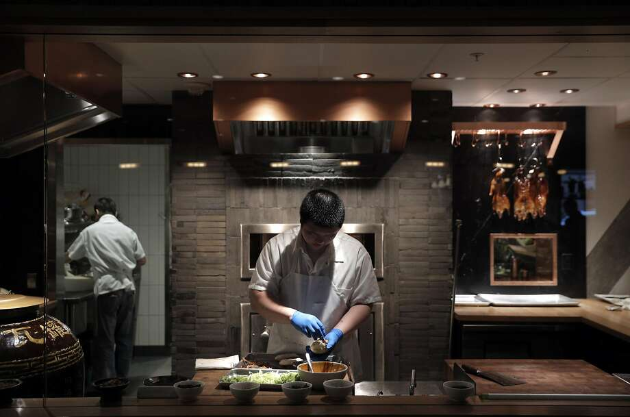 A cook prepares Peking Duck with Kumquat Glaze at the barbecue kitchen at China Live in San Francisco. Photo: Carlos Avila Gonzalez, The Chronicle