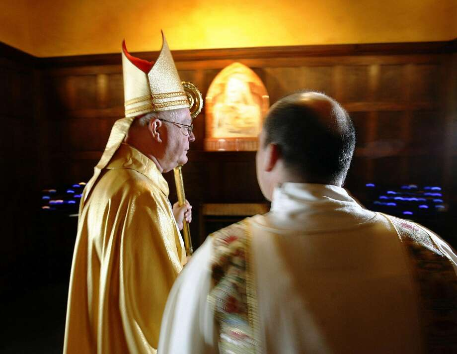 Bishop George Niederauer is illuminated by camera flashes as he makes his way to the sanctuary in his farewell mass in Salt Lake City before coming to San Francisco in 2006. Photo: Steve Griffin, SFC