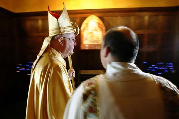 Bishop George Niederauer is illuminated by camera flashes as he makes his way to the sanctuary prior to his farewell mass at The Cathedral of the Madeleine Feb. 5, 2006.l Griffin/photo