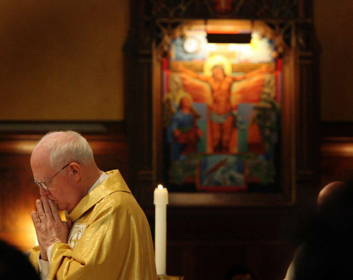 Bishop George Niederauer prays during his farewell mass at The Cathedral of the Madeleine Feb. 5, 2006. Griffin/photo