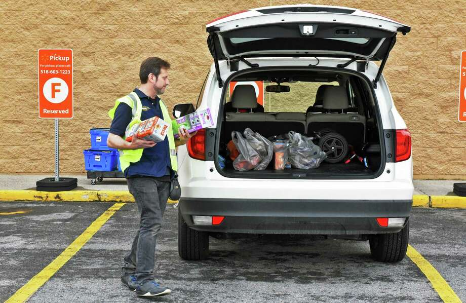 Personal shopper George Whitcomb delivers an order to the pickup parking area at the Walmart in Halfmoon back in May of 2017. Walmart is expanding the service to Glenmont and Amsterdam. (John Carl D'Annibale / Times Union) Photo: John Carl D'Annibale / 20040405A