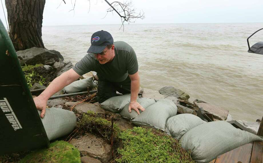 Rob Bauman arranges sandbags along the banks of Lake Ontario on property that belongs to his parents on Edgemere Dr., Tuesday, May 2, 2017, in Greece, N.Y. (Jamie Germano/Democrat & Chronicle via AP) ORG XMIT: NYROD201 Photo: JAMIE GERMANO / Democrat & Chronicle