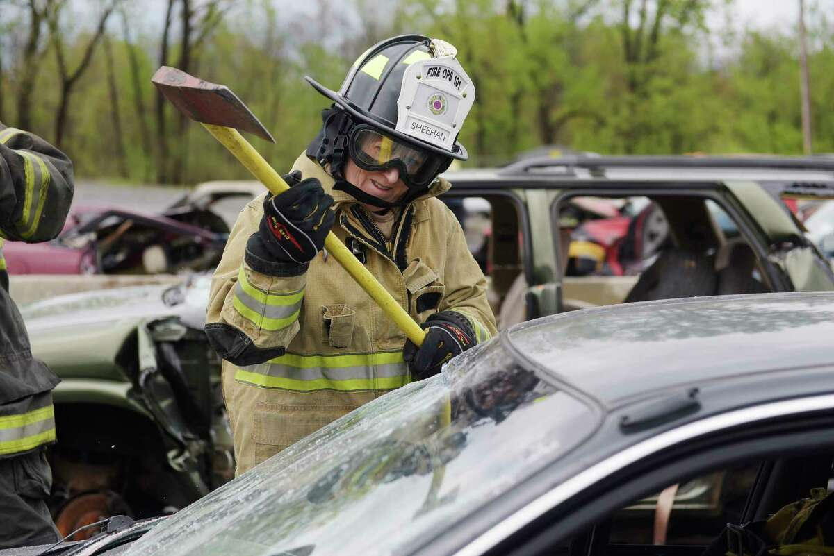 Albany Mayor Kathy Sheehan uses an ax to break away the edges of a windshield at the Colonie Municipal Training Center on Tuesday, May 2, 2017, in Latham, N.Y. Local media representatives along with local and statewide elected officials took part in a hands-on event where they experienced the kind of work firefighters do. (Paul Buckowski / Times Union)