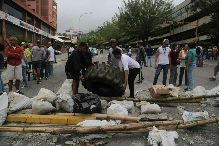 Residents put a tire on a roadblock Tuesday outside their residences in El Hatillo's municipality near Caracas, Venezuela. Photo: Fernando Llano, STF / Copyright 2017 The Associated Press. All rights reserved.