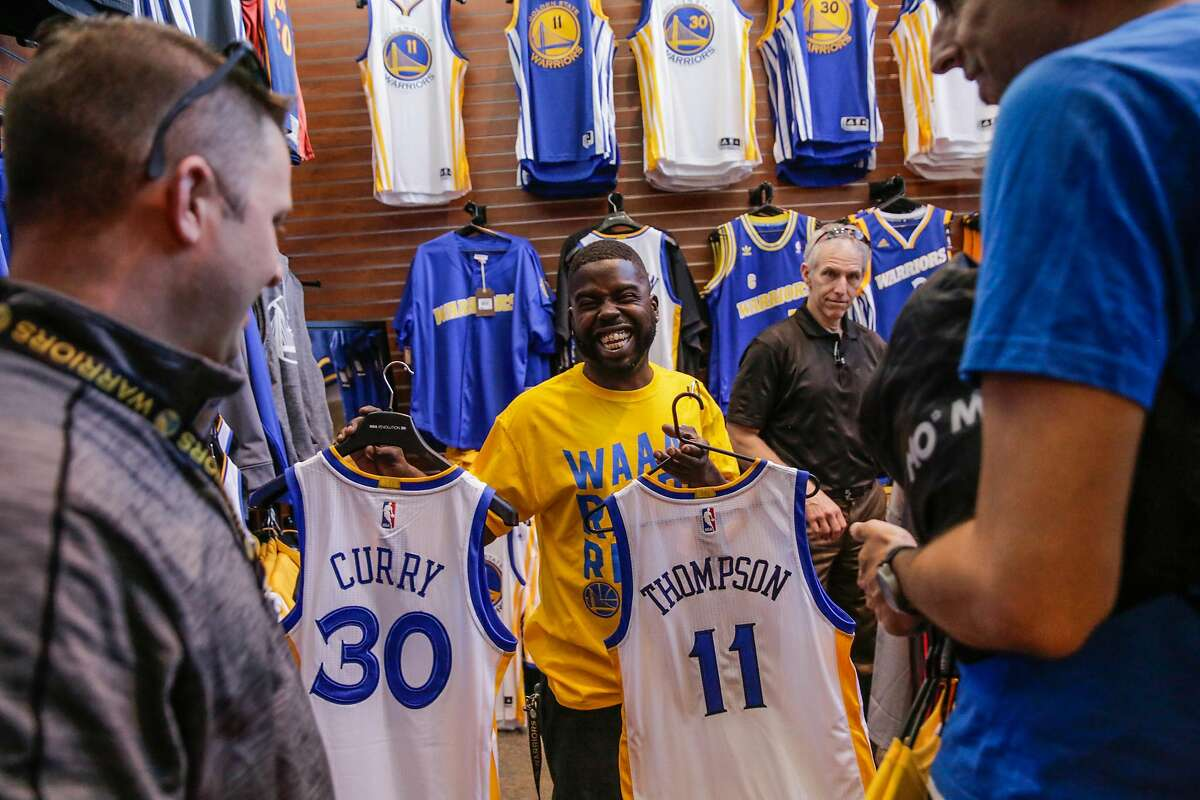 FILE - Eugene Spinks (center) sells jerseys at a Warriors Team Store in Oakland in this file photo from Tuesday, May 2, 2017. The store hosted the Larry O'Brien NBA Championship Trophy on Friday, June 30.