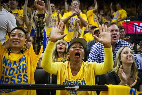 Carolyn Booker (center) cheers during the first half of Game 1 of the Western Conference Semifinals 2017 NBA playoffs between the Golden State Warriors and Utah Jazz at Oracle Arena in Oakland, California, on Tuesday, May 2, 2017.