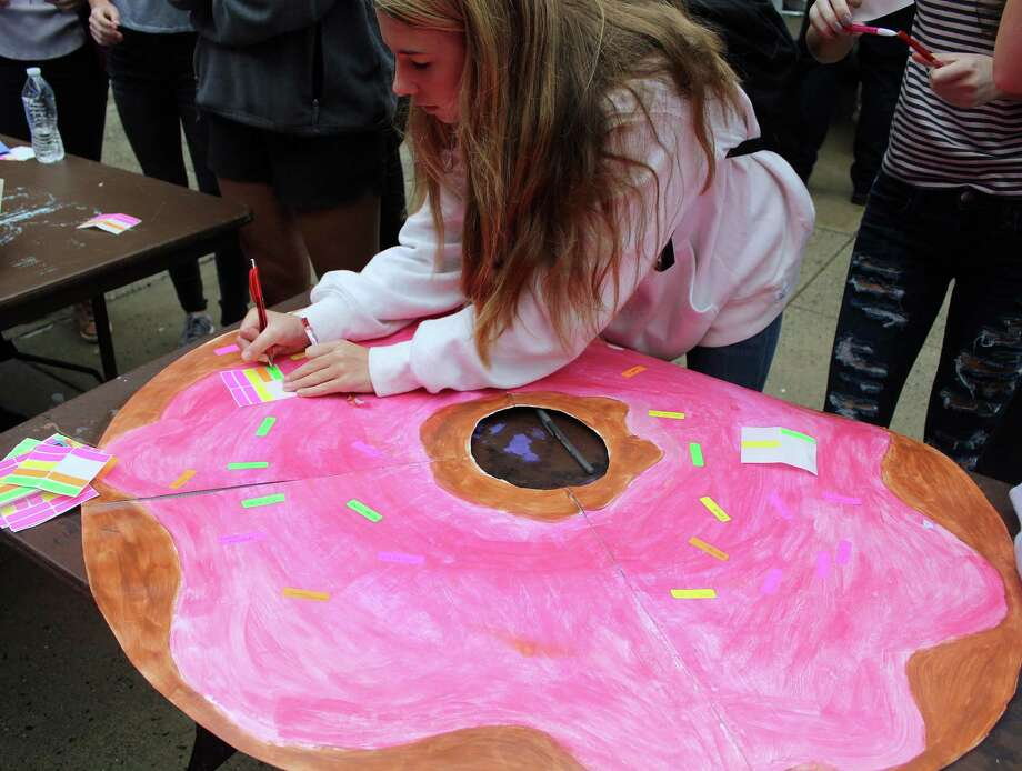 At the Traffic Safety Fair at Darien High School on April 27, 2017 in Darien, CT, students signed a donut as a way of pledging not to drive drunk. Photo: Erin Kayata / Hearst Connecticut Media / Darien News
