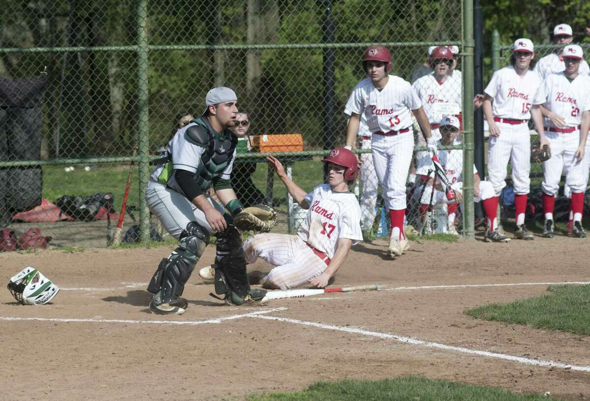 New Canaan's Griffin Arnone slides home to score the winning run as Norwalk catcher Marco Monteiro waits for the ball at Mead Park in New Canaan on Monday. New Canaan won the game 1-0.