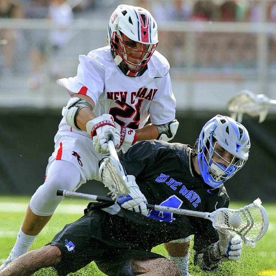 Darien's Logan McGovern maintains control of the ball under pressure from New Canaan's Andrew Bauersfeld on Saturday. Photo: Matthew Brown / Hearst Connecticut Media / Stamford Advocate