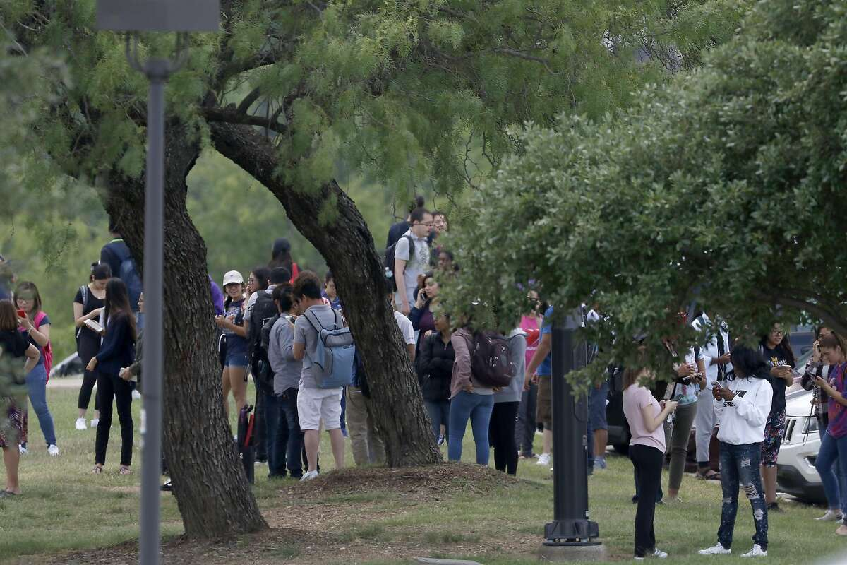 People stand in the parking lot while Irving police officers work at the shooting scene on the North Lake College campus in Irving, Texas, Wednesday, May 3, 2017. (Jae S. Lee/The Dallas Morning News)