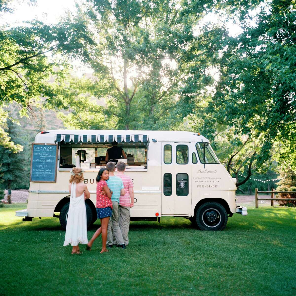 In this 2016 photo provided by Lucky Malone Photography, children line up for desserts from The Bumblebee truck at a wedding held at the Lyon's Farmette & River Bend in Lyons, Colo. The Bumblebee is a dessert truck owned and operated by Denver-based chef Lora Kleinwachter. (Danielle DeFiore/Lucky Malone Photography via AP) ORG XMIT: NYLS310