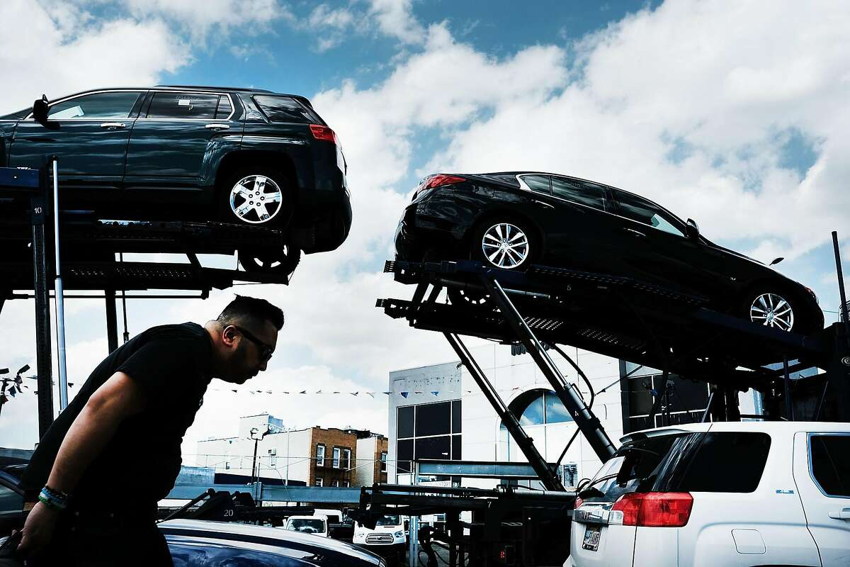 NEW YORK, NY - MAY 02: A man walks by new cars at a Queens auto dealership on May 2, 2017 in New York City. Auto sales continue to slow across the country, one of the few sectors underperforming in the U.S. economy. As signs that demand for cars, trucks and SUVs continue to slow following seven straight years of growth, the big automakers said their U.S. sales fell last month. (Photo by Spencer Platt/Getty Images)
