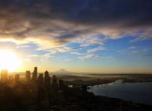 The sun rises over Mount Rainier and the Seattle skyline early Friday morning as seen from the Space Needle.  (Genna Martin, seattlepi.com)