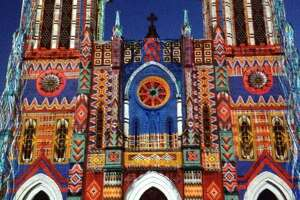 """A photo of the downtown art installment """"The Saga"""" projected on San Fernando Cathedral."""