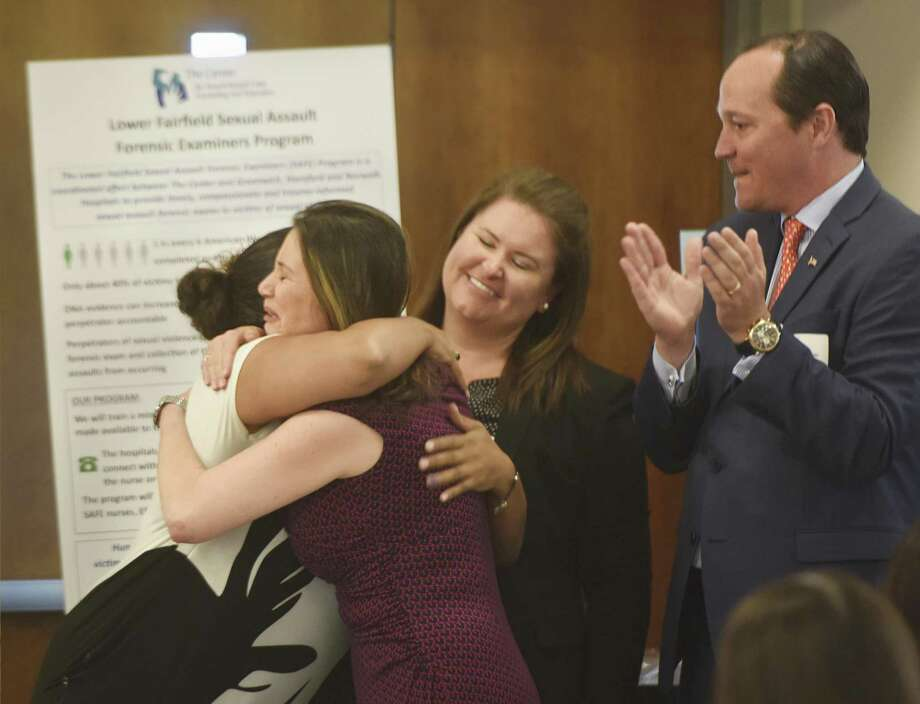Sexual Assault Crisis and Education Center Executive Director Ivonne Zucco hugs Michelle Vincoli, left, as fellow team members Sarah Gleason and Clifton Benham celebrate The Center's $100,000 grant awarded for the Sexual Assault Forensic Examiners (SAFE) Program at Impact Fairfield County's Grant Awards Presentation at the UConn Stamford campus in Stamford, Conn. Wednesday, May 3, 2017. The Sexual Assault Crisis and Education Center won a $100,000 grant for its Sexual Assault Forensic Examiners (SAFE) Program, which will coordinate between The Center and Greenwich, Stamford and Norwalk Hospitals to provide expedited and compassionate sexual assault forensic exams to victims of sexual violence. Photo: Tyler Sizemore / Hearst Connecticut Media / Greenwich Time