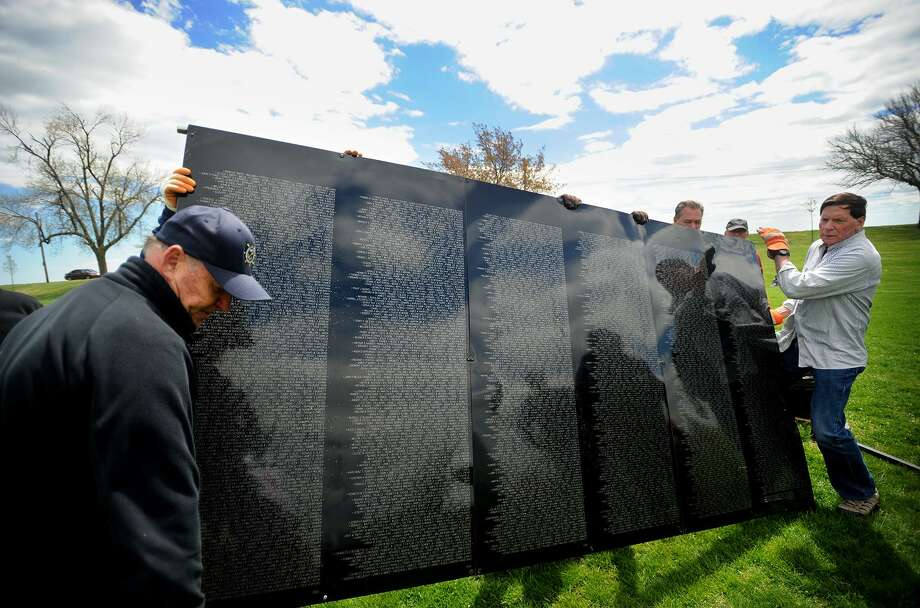 Veterans Ted Terentiuk, left, of Milford, and Bill Repko, right, of Fairfield, join to help assemble The Wall That Heals, a half scale travelling replica of the Vietnam Veterans Memorial, at Seaside Park in Bridgeport, Conn. on Wednesday, May 3, 2017. Photo: Brian A. Pounds / Hearst Connecticut Media / Connecticut Post