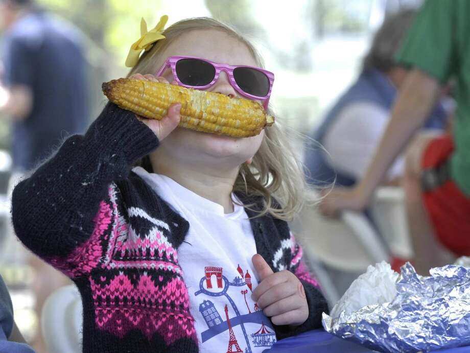 Jane Mulvihill, 3, of Ridgefield, digs into a grilled ear of corn at the Annual Ridgefield Gone Country BBQ Festival, held at Ridgefield's Lounsbury House on Saturday, May 2, 2015. Photo: H John Voorhees III / H John Voorhees III / The News-Times