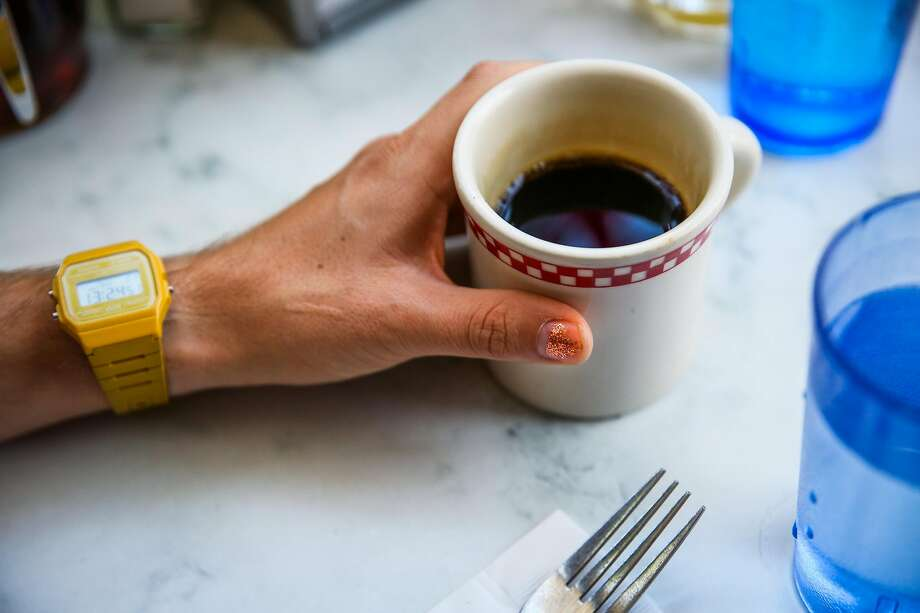 (l-r) Parker Higgins, of San Francisco, grabs a cup of coffee while showing off his Casio watch and bronze sparkly nail polish while eating at brunch spot St. Francis Fountain in San Francisco, California, on Sunday, April 23, 2017. Photo: Gabrielle Lurie / The Chronicle