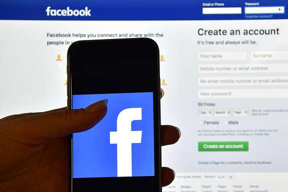 FILE: MAY 3, 2017 - According to reports, Facebook has declared first-quarter earnings of $8 billion, surpassing revenue expectations. The social media company attributed their Q1 earnings to an increase in users and ad revenue. LONDON, ENGLAND - AUGUST 03: A person holds an iPhone displaying the Facebook app logo in front of a computer screen showing the facebook login page on August 3, 2016 in London, England.  (Photo by Carl Court/Getty Images)