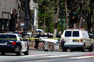 A body is transported to a medical examiner's van after an offcer invovled shooting on the 900 block of Market Street on Wednesday, May 3, 2017 in San Francisco, Calif.